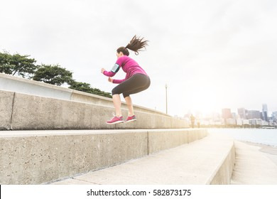 Young woman doing leg exercises with Chicago skyline on background. Beautiful caucasian woman jumping over bis step, squat exercise. Fitness and health concepts