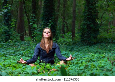 Young woman doing lotus yoga position outside in the forest