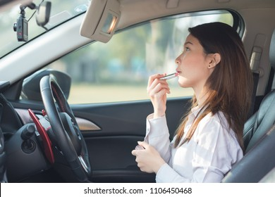 Young woman doing make up in car, painting lipstick