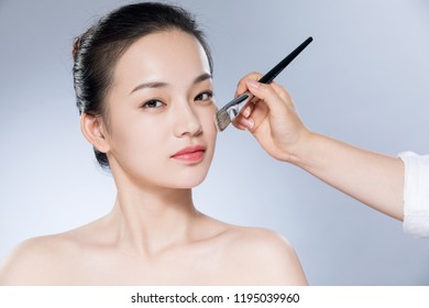Young woman doing makeup.