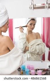 Young woman doing makeup at home.
