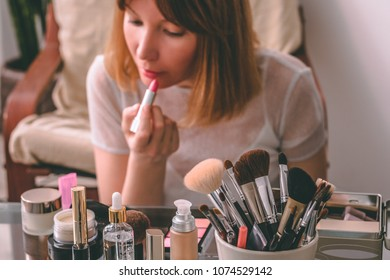Young woman doing make-up, paints her lips with lipstick at table with decorative cosmetics. Home interior.