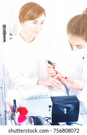Young woman doing manicure in shellac technique in nail salon