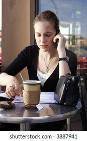 Young woman doing paperwork and talking on cell phone at cafe.