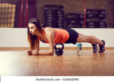 Young woman doing plank exercise at gym