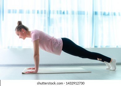 Young woman doing plank and fitness exercises on yoga mat at home. Lose weight and be fit. Sports healthy lifestyle