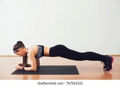 Young woman doing a plank in the studio. Lifestyle and sport concept.
