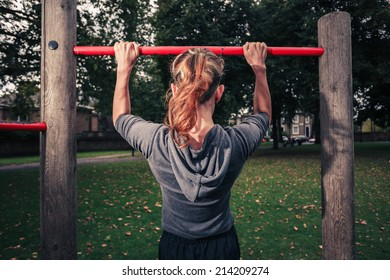 A young woman is doing pull ups in the park