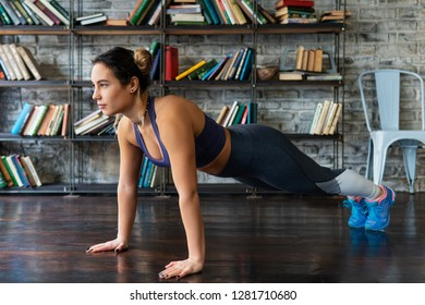 Young woman doing push ups workout during fitness training on floor at home