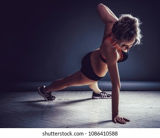 Young Woman Doing Push-Ups. Dark background