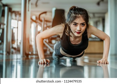 young woman doing push-ups at the gym.