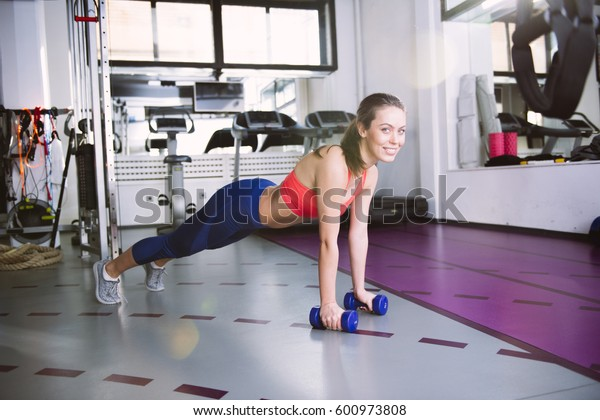 Young woman doing push-ups with weights