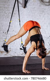 Young woman doing push-ups while legs hanging on trx