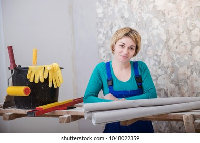 young woman doing repairs in apartment, wallpapering on wall