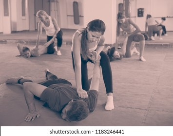 Young woman is doing self-defence moves with trainer in sporty fitness club