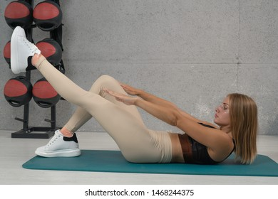 Young woman doing sit ups in the gym on the floor