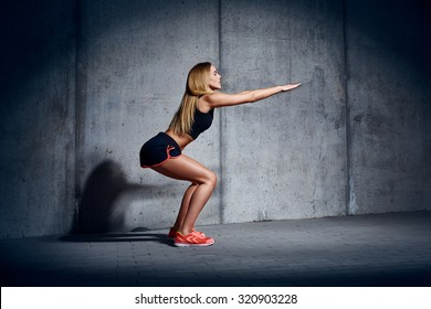 Young woman doing sit ups exersise against concrete wall