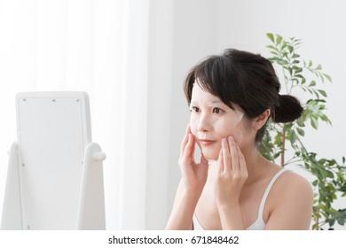 Young woman doing skin care, sheet mask, sheet pack