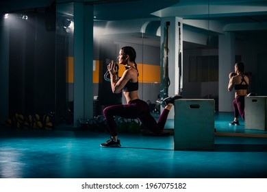 A young woman doing a split squats exercise in the empty gym with weights and other exercise equipment in her surroundings.