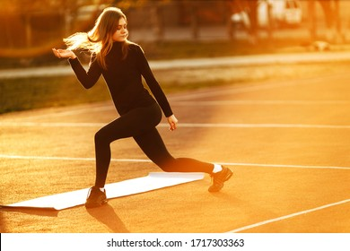 Young woman doing sports exercises isolated at the sports stadium