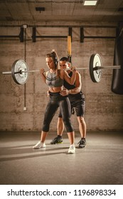 Young woman doing squat exercise at the gym with a personal trainer.