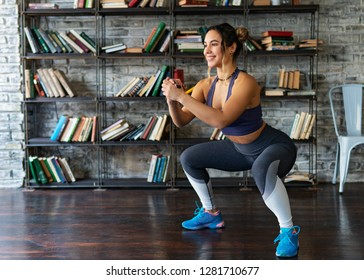 Young woman doing squat workout and smiling during fitness training at home