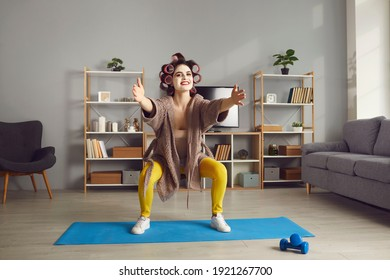 Young woman doing squats exercise. Funny tired housewife in beauty face mask and curlers squatting on fitness mat during sports workout at home. Keeping fit and reaching perfect body concept