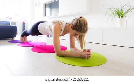 Young woman doing stabilization workout in her living room.