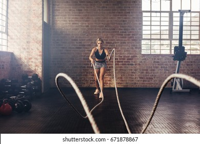 Young woman doing strength training using heavy ropes at the gym. Athlete moving the ropes in wave motion as part of strength training.
