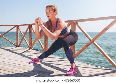 Junge Frau, die sich nach dem Training streckt. Aktiver Lebensstil.