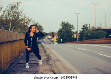 Young woman is doing stretching exercise on the bridge, preparing for workout