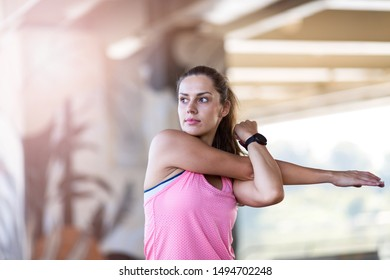 Young woman doing stretching exercise in urban area