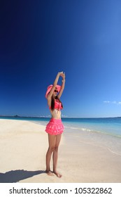 young woman doing stretching exercises on beach