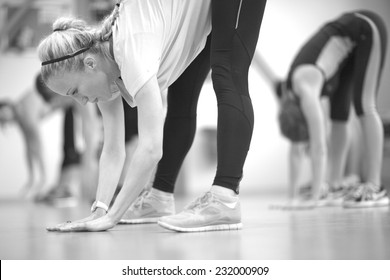 Young woman doing stretching exercises, monochrome