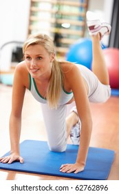Young Woman Doing Stretching Exercises In Gym