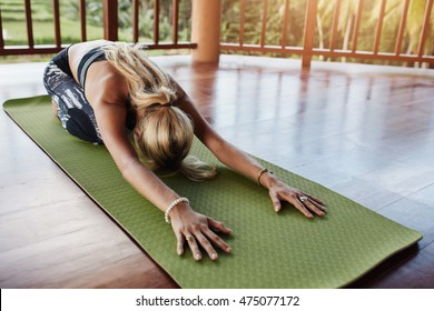 Young woman doing stretching workout on fitness mat. Female performing yoga on exercise mat at gym. Child Pose, Balasana.