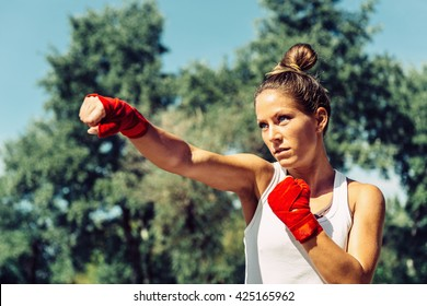 Young woman doing taebo direct punch, focus on eyes