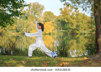 young woman doing a taichi or qi gong exercise at a lake