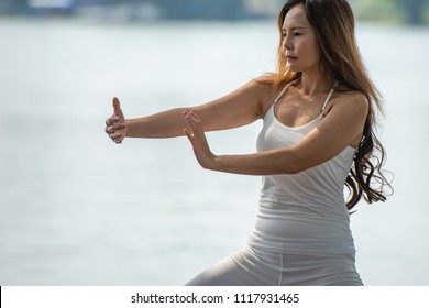 Young woman doing traditional Tai Chi Chuan, Tai Ji and Qi gong in the park for healthy, traditional Chinese martial arts concept.