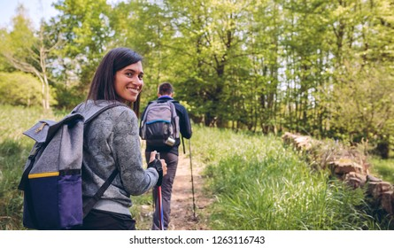 Young woman doing trekking looking at camera with guy in the background