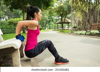 Young woman doing triceps bench dips in the park, side view