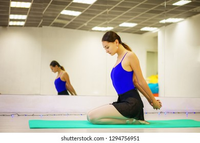 young woman doing warm-up on the Mat in the gym