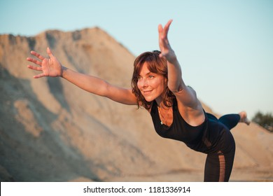 young woman doing warrior 3 yoga pose outdoors