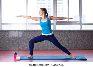 Young woman doing warrior pose in the gym