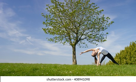 Young woman doing a wild thing yoga pose or Camatkarasana