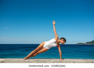 Young woman doing yoga asana Vasisthasana , Side Plank. On the seaside in white bathing suit, concept healthy life, active vacation