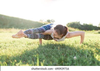 Young woman doing yoga asana ashtavakrasana. Hand standing pose. Yogi workout on green grass on nature outdoor, lifestyle healthy concept