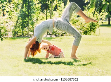 Young woman doing yoga with baby in the summer park. Beautiful mother and daughter like a little buddha exercising on green grass on nature. Family outdoors. Parent with child spend time together.