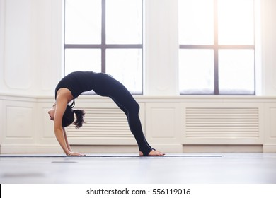 Young woman doing yoga Bridge pose. Asana Chakrasana or Dhanurasana. Beautiful latin woman enjoying yoga indoors in sport clothes, working out in gym class