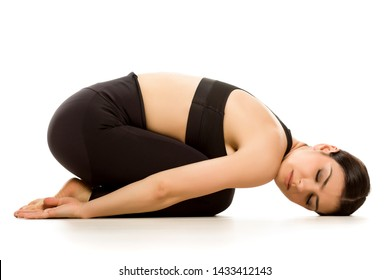 Young woman doing yoga child relaxing pose on white background